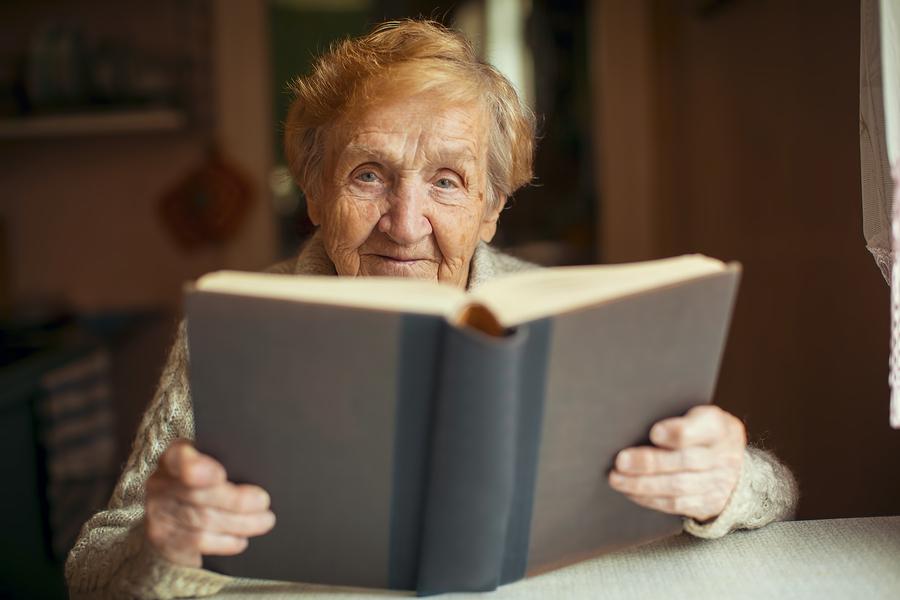 אשה מבוגרת קוראת ספר מודפס