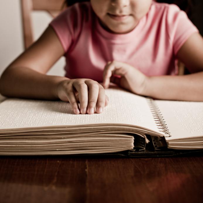 ילדה קוראת ספר ברייל